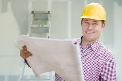 man wearing a hard hat holding large piece of paper, ladder leaning against wall