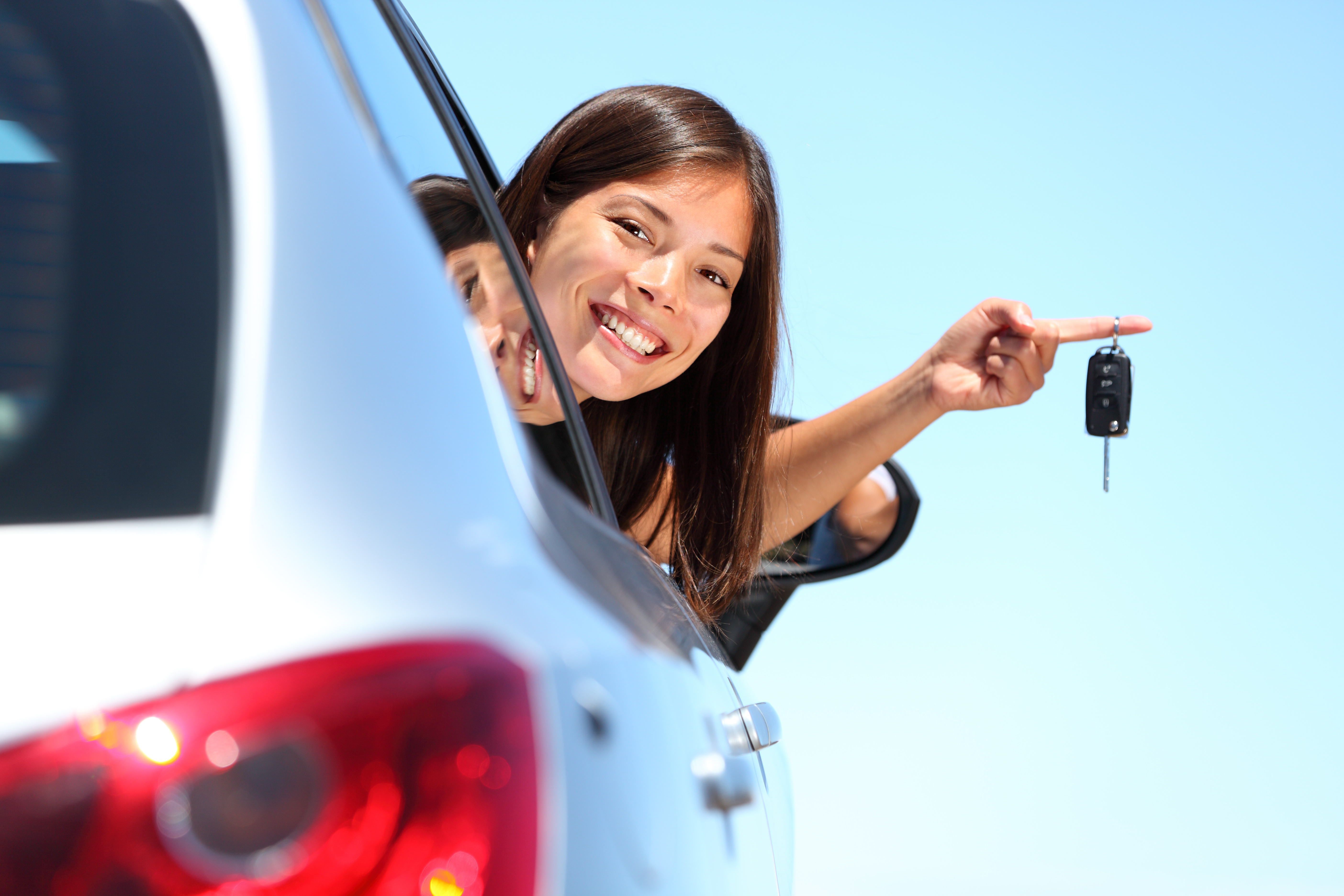 Woman driver holding car keys out window on one finger